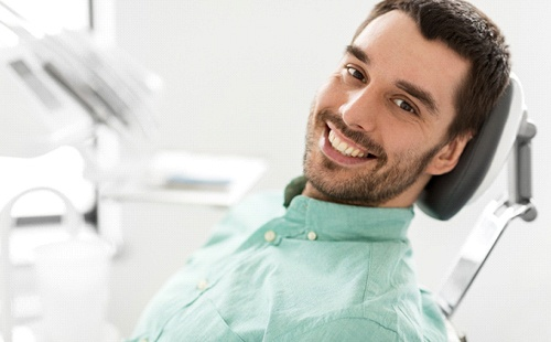 A young man with a beard smiling and waiting to have his metal fillings in Delafield removed