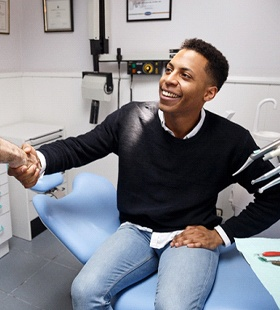 A male patient shakes hands with a dentist after having more aesthetically pleasing fillings put into place
