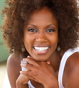A woman wearing a white tank top smiles after receiving her beautiful and natural dental crown