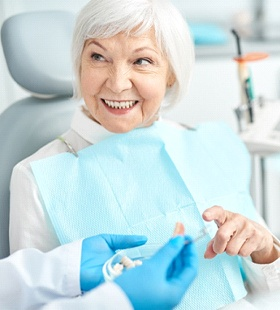 An older woman talking to her dentist about dental implant care in Delafield