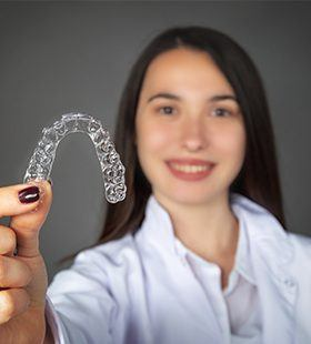 Smiling woman holding up an Invisalign tray