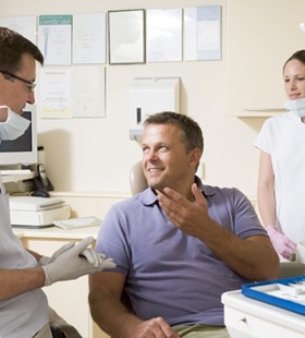 A dentist talking to his male patient